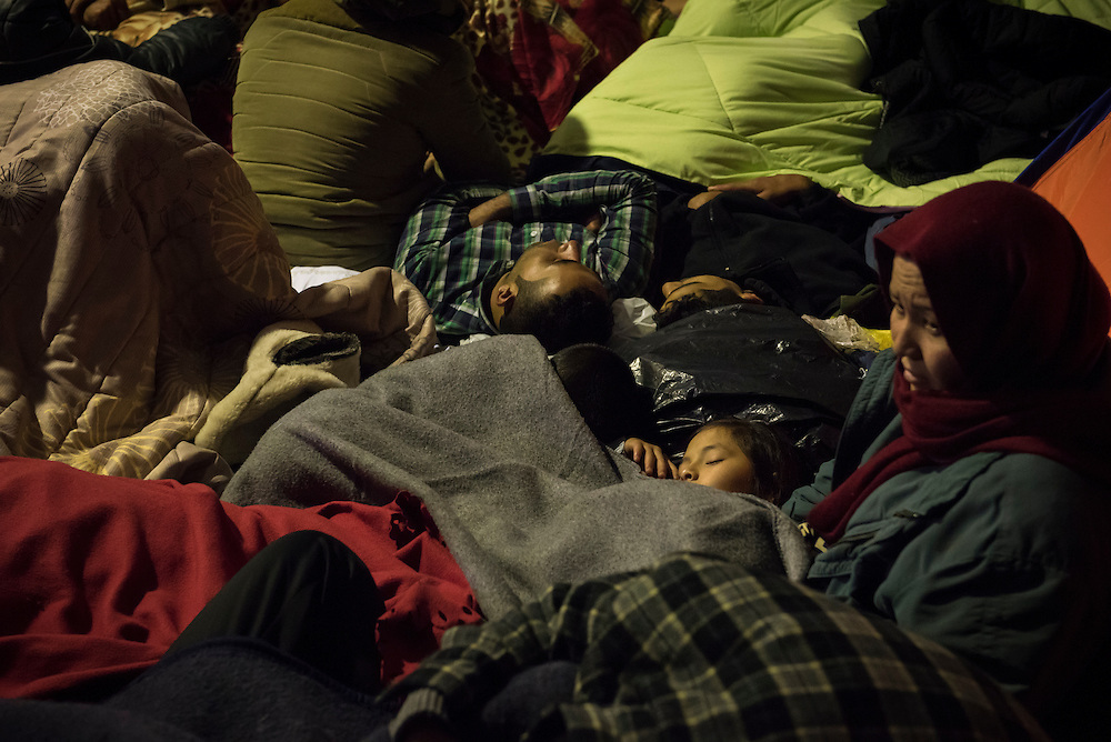 An Afghan woman and child are among a crowd of migrants who, having taken crowded boats from Turkey to the Greek island of Lesbos, wait for a ferry to continue their journey toward the European mainland. Here they sleep at the island's main port, Mytilene.