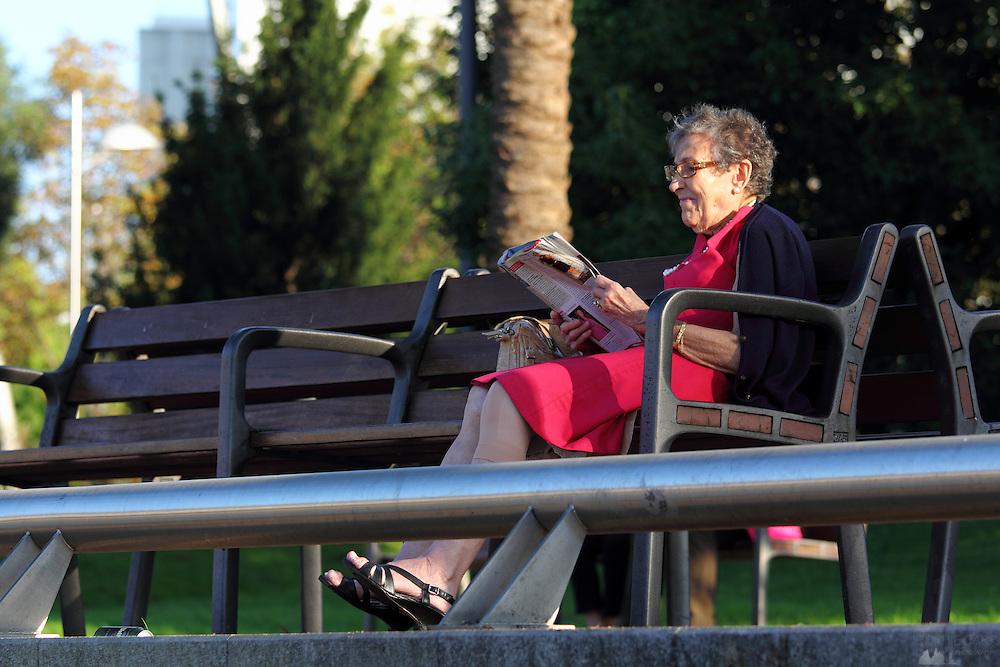 An old woman sits reading a magazine along the Muelle de Evaristo Churruca, a modern walkway along the riverside in Bilbao