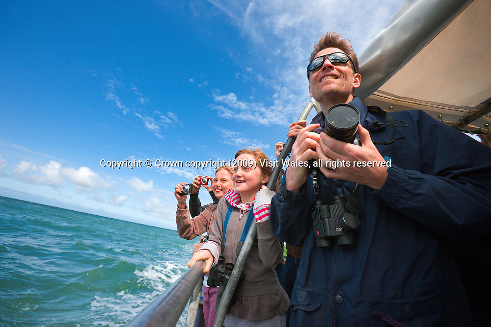 Father and daughter looking through binoculars<br /> Near New Quay<br /> Ceredigion Heritage Coast<br /> Dolphin watching<br /> Activities And Sports