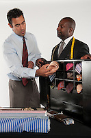 Man selecting neckwear while shop owner standing besides him