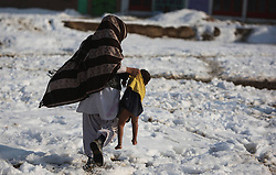 An Afghan carries a child in Kabul, Afghanistan, on Jan. 13, 2013. More than 8.4 million Afghan children, of whom 39 percent are girls, presently attend school, while 4.2 million others have no access to school mainly due to security reasons and poverty, January 13, 2013. Photo by Imago / i-Images...UK ONLY