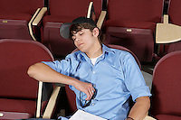 male college student sleeping in classroom