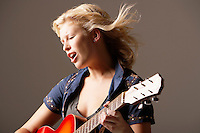 Woman Playing Guitar and Singing with windblown hair close-up