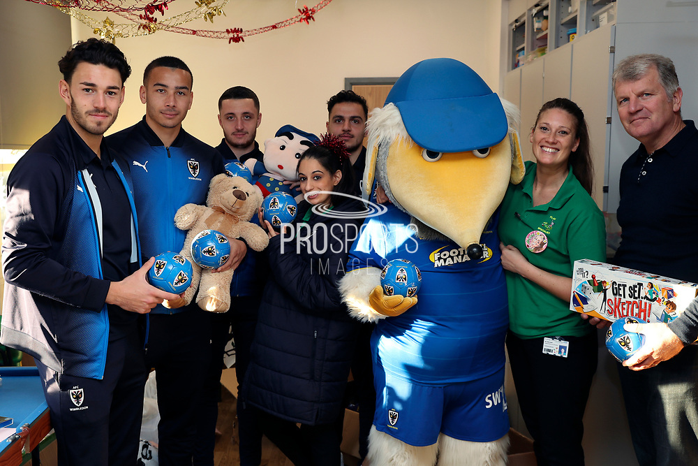AFC Wimbledon defender Will Nightingale (5), AFC Wimbledon attacker Egli Kaja (21), AFC Wimbledon midfielder Anthony Hartigan (8), AFC Wimbledon defender Rod McDonald (26) and AFC Wimbledon first team coach Glyn Hodges delivering Christmas presents to the children on behalf of AFC Wimbledon, at St George's Hospital, Tooting, United Kingdom on 13 December 2018.