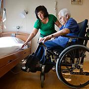 Foto: David Rozing NIET VOOR LANDELIJKE KRANTEN. Nederland Rotterdam 16 augustus 2013 20130816 Verpleegster helpt oude mevrouw met oefeningen instappen en uitstappen van de rolstoel in haar kamer in verzorgingshuis. Foto: David Rozing