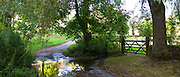 Stream ford crosses country lane rural scene in Swinbrook in The Cotswolds, England, United Kingdom