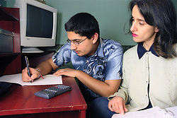 Single mother helping teenage son with maths homework,