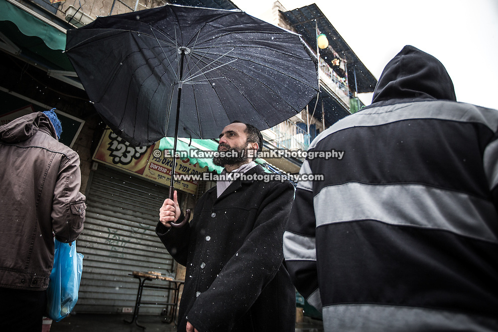 A man walks with an umbrella during a snow storm at The Mahane Yehuda Shuk on January 9, 2015 in Jerusalem, Israel. (Photo by Elan Kawesch)