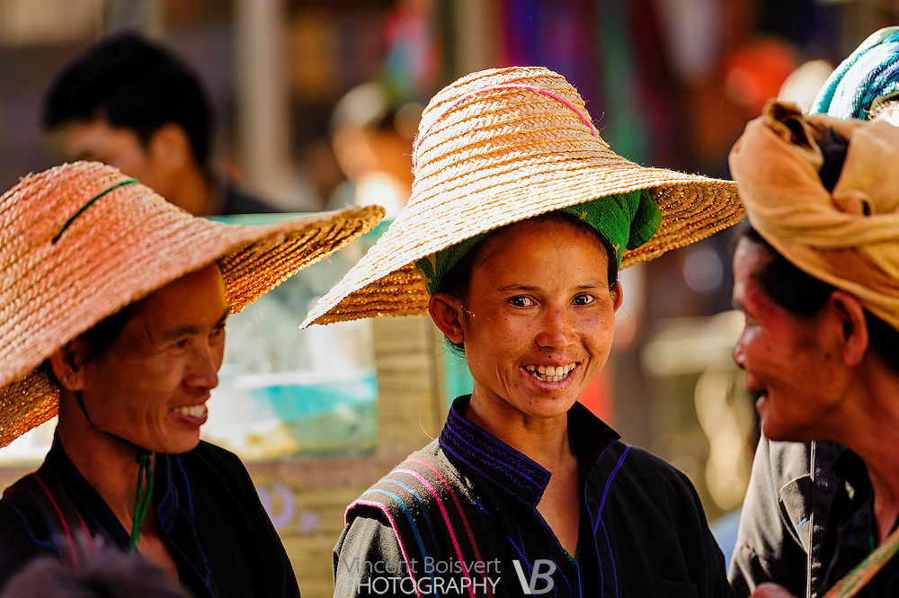 a Shan woman wearing a green towel and a traditional straw hat on a market day around Inle lake, myanmar
