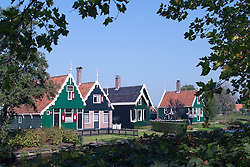 """Dutch architecture gets almost whimsical in this open-air historical museum. Zaanse Schans is a popular day trip for Amsterdam visitors.  .From Wikipedia: """" Zaanse Schans is a neighbourhood of Zaandam, near Zaandijk in the municipality of Zaanstad in the Netherlands, in the province of North Holland. It has a collection of well-preserved historic windmills and houses; the ca. 35 houses from all over the Zaanstreek were moved to the museum area in the 1970s. The Zaans Museum, established in 1994, is located in the Zaanse Schans..The Zaanse Schans is one of the popular tourist attractions of the region and an anchor point of ERIH, the European Route of Industrial Heritage. The neighbourhood attracts approximately 900,000 visitors every year..The windmills were built after 1574."""".Also from Wikipedia: """" Along the river Zaan, you can find still dozens of original windmills (mostly entirely made of wood), still technically functioning, some of them over 350 years old. Next to these there are many 19th century stone industrial buildings, nowadays derelict or converted into apartments, but still recognisable as industrial buildings.""""."""
