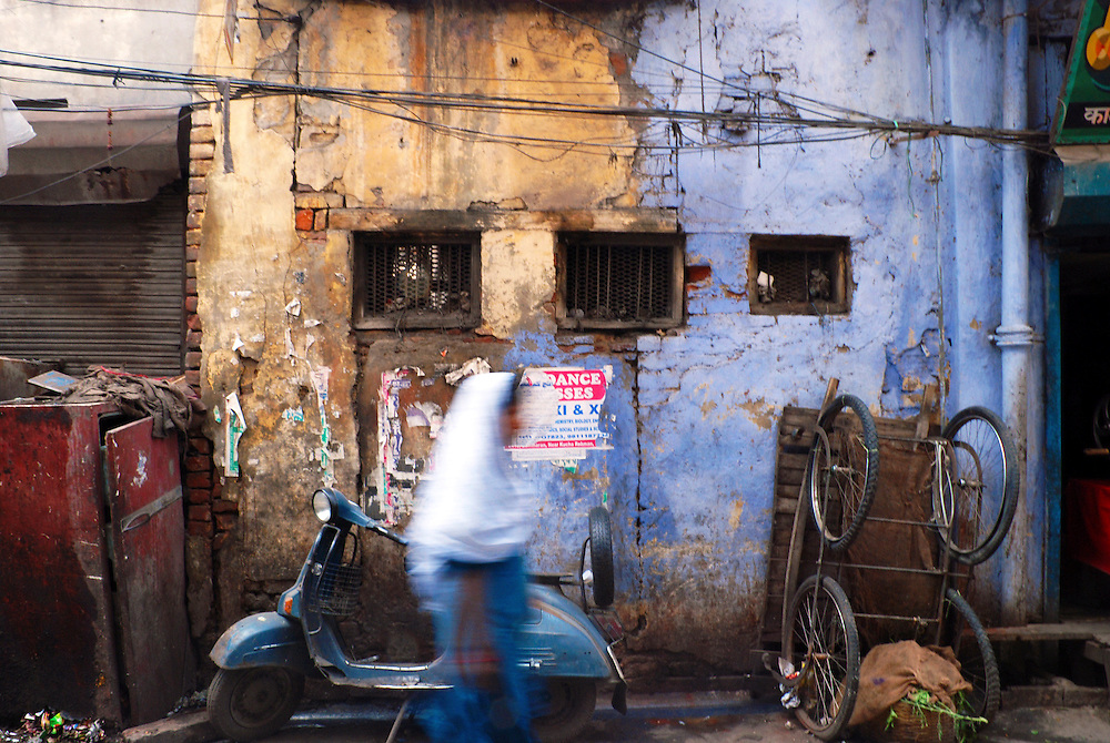 Old Delhi, India. 2007<br /> <br /> A muslim woman in blue and white passes by a colorful wall in a market of Old Delhi, India