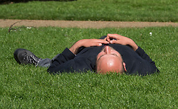 © Licensed to London News Pictures. 04/05/2018. London, UK. A man takes a nap in the sunshine in St James's Park in central London. High temperatures are expected to continue throughout the bank holiday weekend. Photo credit: Peter Macdiarmid/LNP