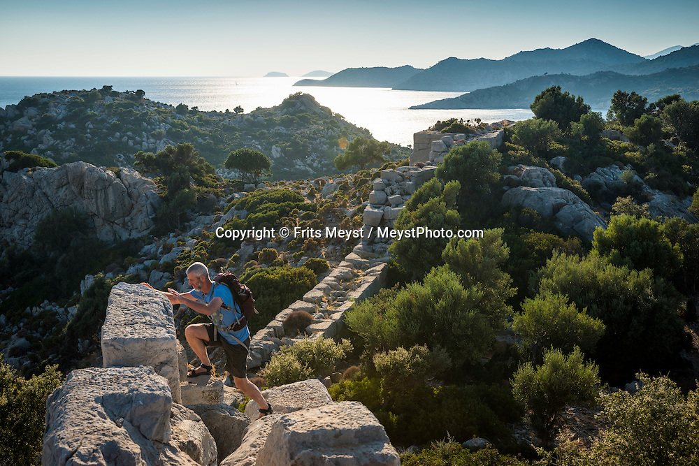 Bozukkale, Bozburun, Turkey, October 2015. After hitching a ride with a fisherman and his wife, we hike from Bozukkale (Loryma) back to Bozburun. Situated roughly between the seaside resorts of Marmaris and Bodrum and the Latmos mountains in the east lies Ancient Caria. The Carian Trail runs through pine scented forests along the coastal mountains of Western Turkey and is littered with ancient ruins, secluded coves with turquoise waters and little villages. more than 800km of ancient roads, shepherd paths and forest trails form Turkey's longest hiking trail. Photo by Frits Meyst / MeystPhoto.com