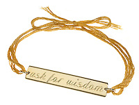 gold ask for wisdom pendant on a yellow string bracelet