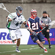 Will Mangan #21 of the Boston Cannons runs with the ball past Dan Burns #4 of the Chesapeake Bayhawks during the game at Harvard Stadium on April 27, 2014 in Boston, Massachusetts. (Photo by Elan Kawesch)