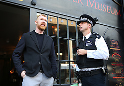 © Licensed to London News Pictures. 04/10/2015. London, UK. Police talk to  Mark Palmer-Edgecumbe (L), owner of the Jack the Ripper Museum, after a planned protest was cancelled as organisers feared a large amount of arrests. Photo credit: Peter Macdiarmid/LNP