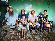 02 JUNE 2015 - KULAI, JOHORE, MALAYSIA: MOHAMED SHAFI bin HABE, one of the leaders of the Rohingya community in Kulai, Malaysia in his home with his family. The UN says the Rohingya, a Muslim minority in western Myanmar, are the most persecuted ethnic minority in the world. The government of Myanmar insists the Rohingya are illegal immigrants from Bangladesh and has refused to grant them citizenship. Most of the Rohingya in Myanmar have been confined to Internal Displaced Persons camp in Rakhine state, bordering Bangladesh. Thousands of Rohingya have fled Myanmar and settled in Malaysia. Most fled on small fishing trawlers. There are about 1,500 Rohingya in the town of Kulai, in the Malaysian state of Johore. Only about 500 of them have been granted official refugee status by the UN High Commissioner for Refugees. The rest live under the radar, relying on gifts from their community and taking menial jobs to make ends meet. They face harassment from Malaysian police who, the Rohingya say, extort bribes from them.     PHOTO BY JACK KURTZ