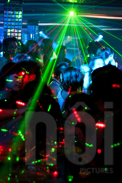 Young Vietnamese drink and dance under lasers in a nightclub in Hanoi, Vietnam