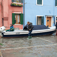 A boat sails along houses in a usually dry place in Burano. More than 59% of Venice was under water on Thursday, as the historic lagoon town was hit by exceptionally high tides. The sea level rose above 140cm overnight and was expected to remain above critical levels for about 15 hours.