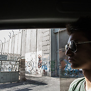 Omar, palestinian circus performer, on the Mobile Circus bus, arriving in Hebron. Behind him, the separation wall between palestinian and israeli sides.