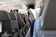 airplane passenger reading news paper while in flight