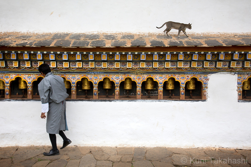 A man rolls prayer wheels at the Chime Lhakhang Temple in Lobsa village near Punakha, Bhutan on September 3, 2013. The village monastery was built in honor of Lama Drukpa Kunley who lived in the 15-16th century and who was popularly known as the &quot;Mad Saint&quot; or &ldquo;Divine Madman&rdquo; for his unorthodox ways of teaching.<br /> (Photo by Kuni Takahashi)