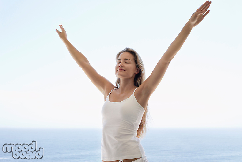 Young woman with arms outstretched and eyes closed on beach