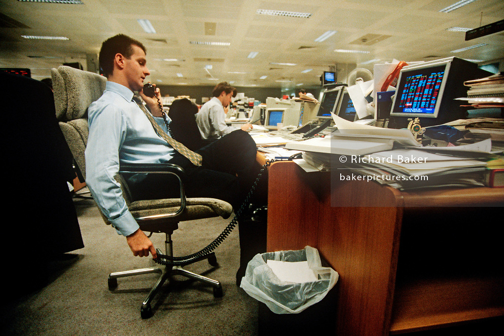A 1990s banker speaks on the phone and in front of his computer, on the trading floor of credit Lyonnais in the City of London (aka The Square Mile), the capital's financial centre, on 20th May 1993, in London, England. (Photo by Richard Baker / In Pictures via Getty Images)