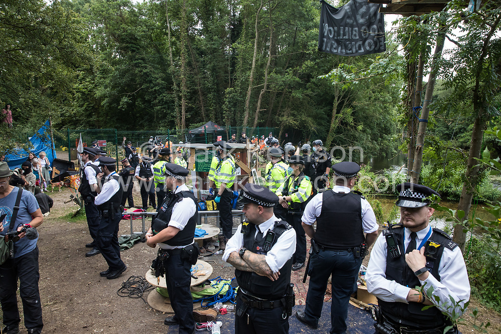 Denham, UK. 24 July, 2020. Police officers from the Metropolitan Police and City of London Police occupy one bank of the river Colne to prevent environmental activists from HS2 Rebellion from attempting to hinder the destruction of an ancient alder tree in connection with works for the HS2 high-speed rail link in Denham Country Park. A large policing operation involving the Metropolitan Police, Thames Valley Police, City of London Police and Hampshire Police as well as the National Eviction Team was put in place to enable HS2 to remove the tree.
