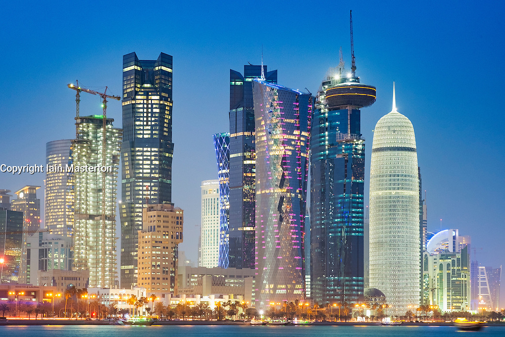 Night view of skyline along waterfront of Corniche towards modern office towers in West Bay district in Doha Qatar
