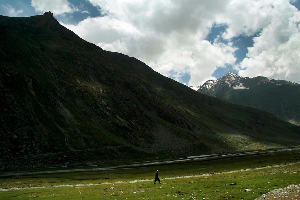A man walking alone in a mountain valley in Kachemir. Photo by Lorenz Berna