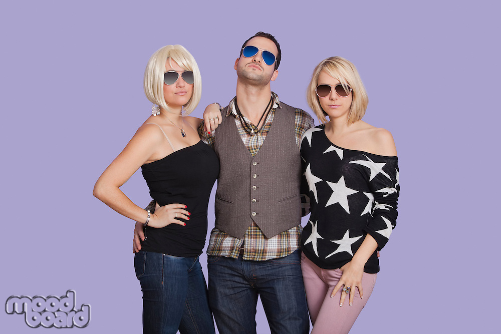 Portrait of man with two beautiful women over purple background