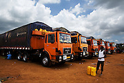 A man stands by a row of large trucks parked at the Terminal du Sahel, a large truck terminal in Lome, Togo on Wednesday October 1, 2008.