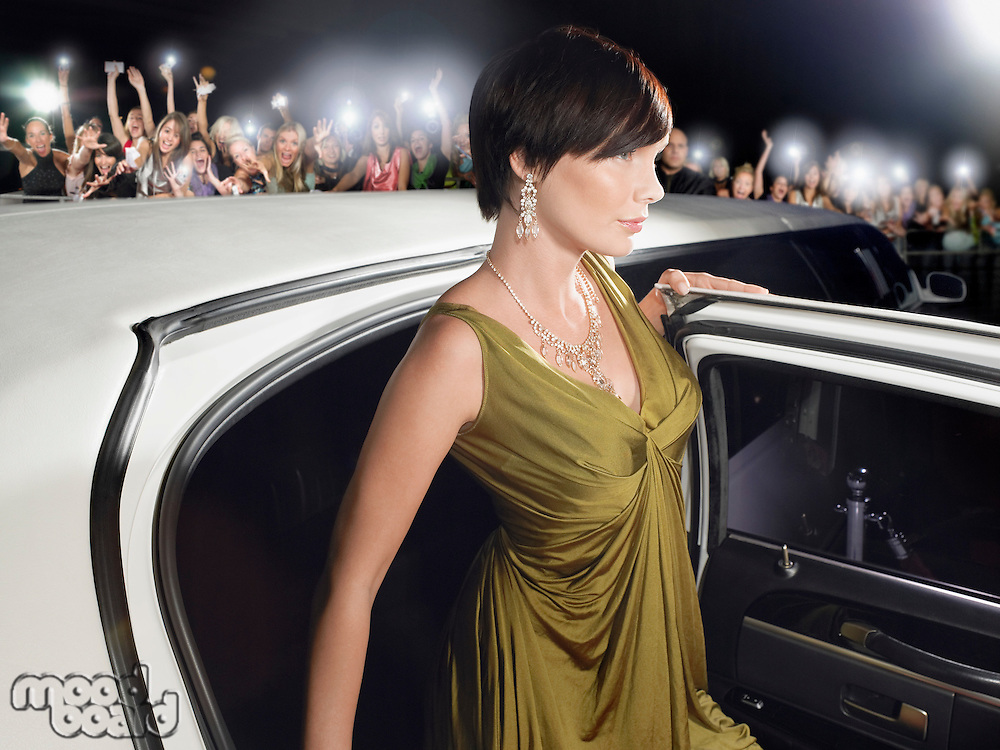 Woman in evening wear getting out of limousine in front of fans and paparazzi