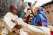 Habsita Moussa, 30, helps her sons Moustapha, 3, and Ibrahim, 5, get dressed after bathing at home in Mongo, Guera province, Chad on Wednesday October 17, 2012.