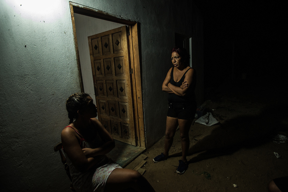 FALCÓN, VENEZUELA - SEPTEMBER 25, 2016: Maria Piñero is woken up in the middle of the night by a phone call from her son Roger, saying that there were rumors in La Vela that another smuggler's boat had just sunk and several people died. Ms. Piñero woke everyone up to share the news, as they spent the night at the safe house while they waited for the smuggler's boat to arrive that will illegally take them from Venezuela to Curaçao. Undocumented migrants here have mortgaged property, sold kitchen appliances and eeven borrowed money from the same smuggling rings that pack them on the floorboards alongside drugs and other contraband. The journey to Curaçao takes them on a 60-mile crossing filled with backbreaking swells, gangs of armed boatmen and coast guard vessels looking to capture migrants and send them home. Then, after being tossed overboard and left to swim ashore, they hide in the brush to meet contacts who spirit them anew into the tourist economy of this Caribbean island. They clean the floors of restaurants, work in construction, sell trinkets on the street, or even solicit Dutch tourists for sex. But at least, the migrants say, there is food. PHOTO: Meridith Kohut for The New York Times