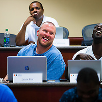 MIAMI, FL - June 24, 2015 -- NFL players for the Miami Dolphins Jason Fox, left, and Michael Thomas, right, share a laugh during a Legal & Ethical Implications of Executive Decision Making class taught by Professor Patricia Abril at the University of Miami as part of their Miami Executive MBA for Artists & Athletes program on Wednesday, June 24, 2015.  (PHOTO / CHIP LITHERLAND)