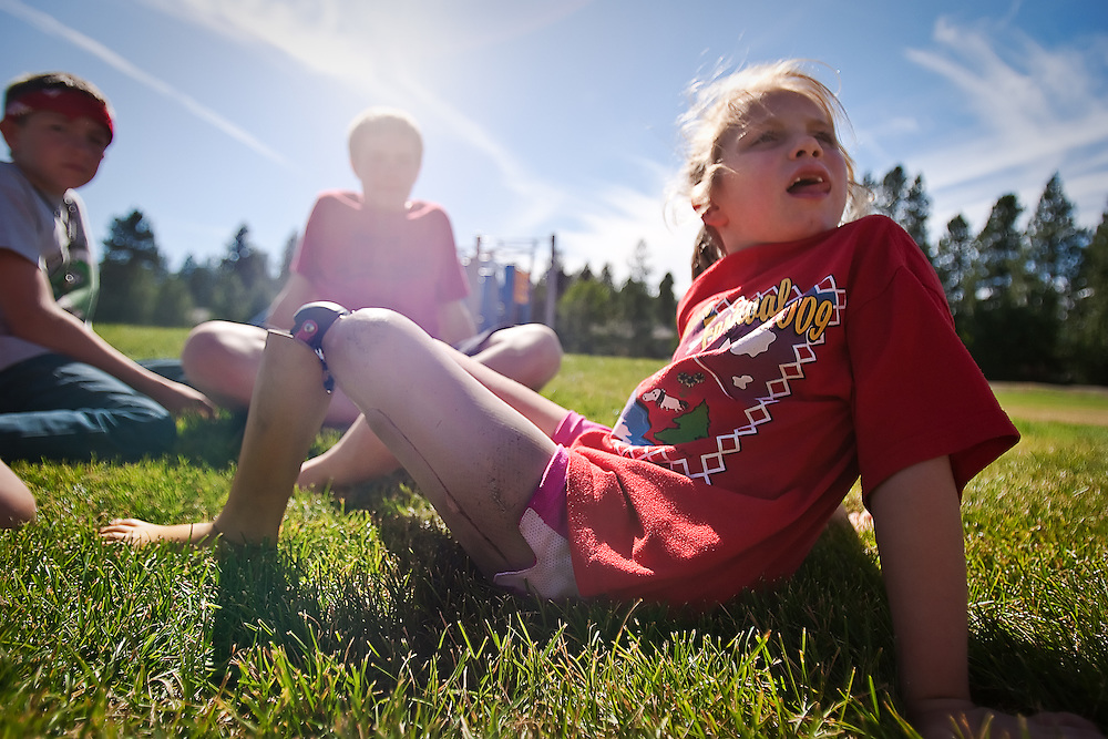 Isabelle James, panting after a hard day of soccer camp, gets a chance to kick back and relax without her cleats and shinguards at Ramsey Park on Friday afternoon.