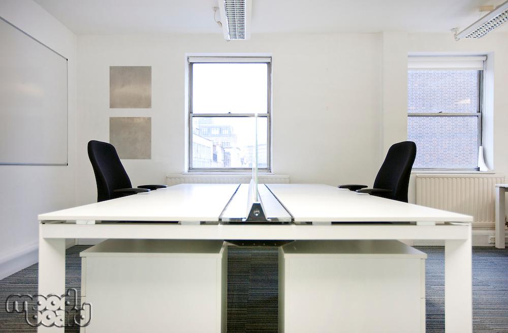Empty office desks back to back