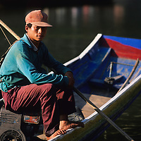 Fisherman poses in boat, Ban Pak Ou, Luang Phrabang, Laos