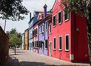 "Brightly painted blue, pink, purple, red, and orange houses. Burano, known for knitted lacework, fishing, and colorfully painted houses, is a small archipelago of four islands linked by bridges in the Venetian Lagoon, in the Veneto region of Italy, Europe. Burano's traditional house colors are strictly regulated by government. The Romans may have been first to settle Burano. Romantic Venice (Venezia), ""City of Canals,"" stretches across 100+ small islands in the marshy Venetian Lagoon along the Adriatic Sea in northeast Italy, between the mouths of the Po and Piave Rivers. Venice and the Venetian Lagoon are honored on UNESCO's World Heritage List."