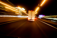 A truck speeds down the highway at night.  Blurred motion.