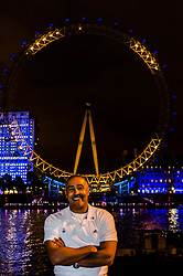 © Licensed to London News Pictures. 19/07/2012. London,UK.  London Eye Light Show.  Decathalon winner Daley Thompson stands smiling before the London Eye illuminated with a huge smiley face.  EYE ON THE GAMES: Daley Thompson kicks off the world's first social media driven light show at the EDF Energy London Eye, powered by the UK's tweets on London 2012. The first EDF Energy of the Nation result reveals the nation is 62% positive about the Games with a week to go.    www.edfenergyofthenation.com  . Photo credit : Richard Isaac/LNP