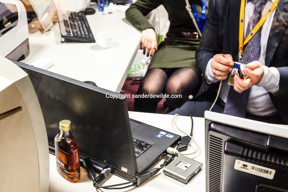 Russian President Vladimir Putin visits the European Council at an European Union-Russia summit in Brussels December 21, 2012. A journalist talk in front of computerscreens. A bottle of wodka stands behind a laptop.
