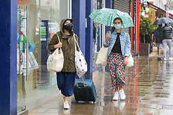 © Licensed to London News Pictures. 27/06/2020. London, UK. A woman wearing face covering shelters from rain underneath an umbrella in north London following a very hot week which saw highest temperature of the year so far. Photo credit: Dinendra Haria/LNP