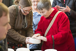 Visually impaired people with carers on outing to Denby Pottery. Woman with volunteer, pushing clay into mould.
