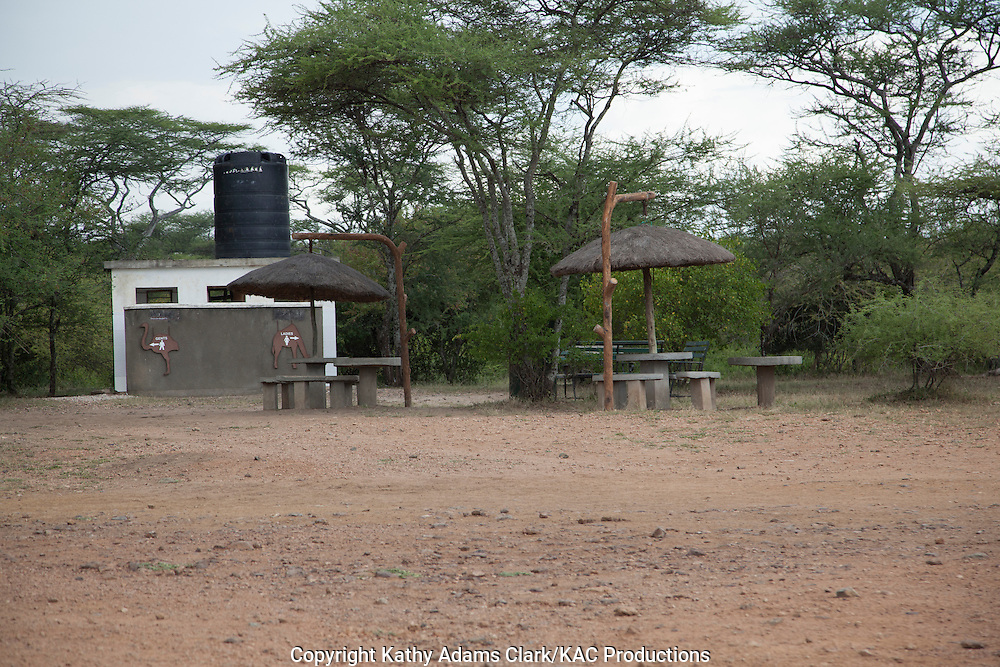 Rest area for tourists in Serengeti, Tanzania, Africa, with restrooms and picnic tables.
