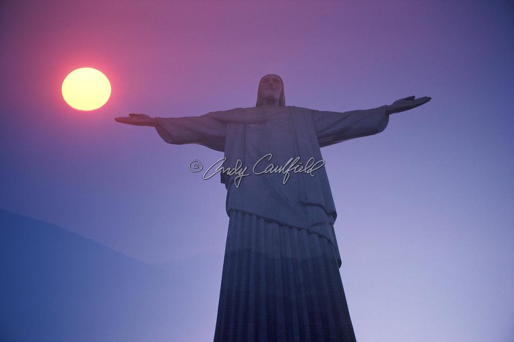 Christ statue with setting sun and Corcovado mountain silhouette (composite). Rio de Janeiro, BRAZIL...