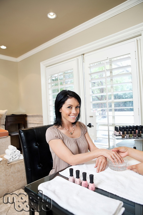 Portrait of a cheerful mid adult woman getting nails polished