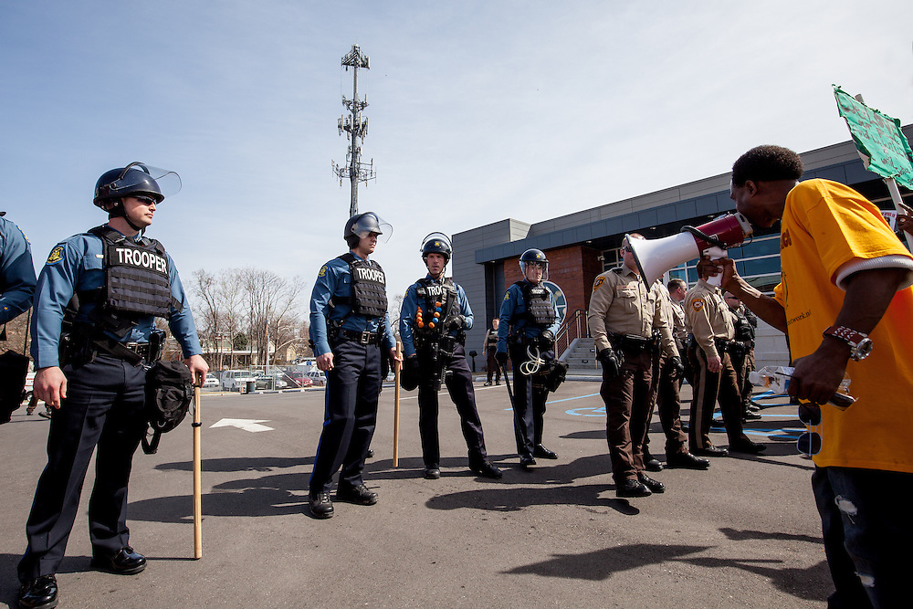 Protesters square off with law enforcement officers in front of the Ferguson police department.